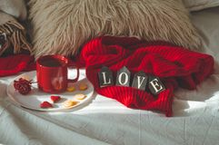 Red cup of tea with kumquat on the plate and two hearts cookies with the word LOVE on a white bed. Valentines day concept. Cozy Home stock photo