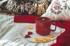 Red cup of tea with kumquat and two hearts cookies on a white bed. Cozy Home. Valentines day concept stock photo