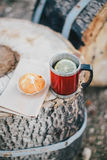 Red cup with tea and lemon and cookies on a wooden log Royalty Free Stock Photos
