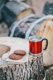 Red cup with tea and lemon and cookies on a wooden log Royalty Free Stock Images