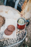 Red cup with tea and lemon and cookies on a wooden log Royalty Free Stock Photo