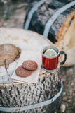 Red cup with tea and lemon and cookies on a wooden log Stock Images