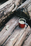 Red cup with tea and lemon and cookies on a wooden log Royalty Free Stock Image