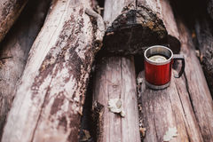 Red cup with tea and lemon on a wooden log Royalty Free Stock Images