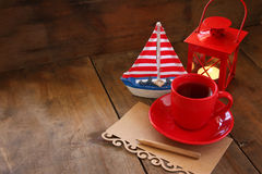 Red cup of tea and letter paper next to vintage decorative boat and lantern on wooden old table. retro filtered image Royalty Free Stock Photo