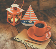 Red cup of tea and letter paper next to vintage decorative boat and lantern on wooden old table. retro filtered image Stock Image