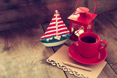 Red cup of tea and letter paper next to vintage decorative boat and lantern on wooden old table. retro filtered image Royalty Free Stock Image