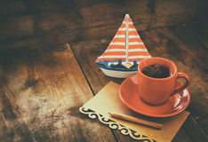 Red cup of tea and letter paper next to vintage decorative boat on wooden old table. retro filtered image.  Royalty Free Stock Images