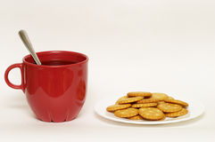 Red cup with tea and plate of crackers Royalty Free Stock Photo