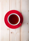 Red cup with tea on saucer Royalty Free Stock Photography