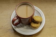 A red cup of tea and two biscuits. A shot from above of a red cup of tea and two biscuits on a white plate which is on a wooden table royalty free stock photography