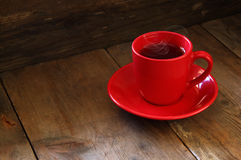 Red cup of tea on wooden old table. retro filtered image Stock Photos
