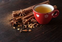 Winter hot tea with spice. Red cup of tea on a wooden table with aromatic winter flavors, cinnamon, cloves and anise stock images