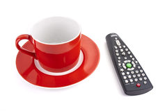 Red cup and TV remote control. Isolated Stock Image