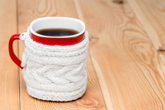 Red cup in white knitted sweater with hot tea. On wooden boards Royalty Free Stock Photography