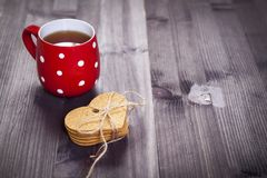 The Red cup in a white point is on a white wooden table. Paper hearts hang on the wall Royalty Free Stock Photos