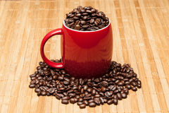 Red cup with whole  beans. Red cup with whole coffee beans Royalty Free Stock Photography
