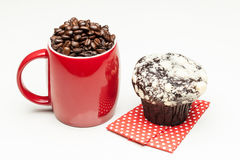 Red cup with whole  beans. Red cup with whole coffee beans and muffin Stock Image