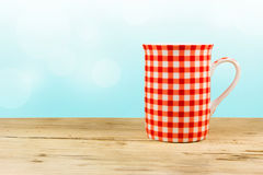 Red cup on wooden table. Royalty Free Stock Images