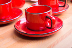Red Cup on wooden table. Cups on table are some pieces in cafe Royalty Free Stock Image
