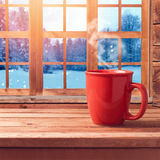 Red cup on wooden table over window with winter nature view. Winter and Christmas holiday concept. Cup mock up template for logo s Stock Photography
