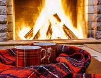 Red  cups  for  hot tea and cozy  warm scarf near  fireplace. Red  cups  for  hot tea and cozy  warm scarf near  fireplace, in country house, winter vacation Royalty Free Stock Photo