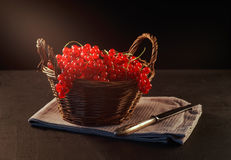 Red currant in basket on black wooden table Royalty Free Stock Images