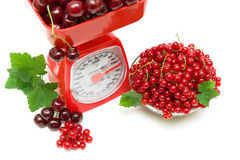 Red currant berries, cherries and kitchen scale on white backgro Stock Photos