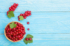 Red currant berries in a wooden bowl with leaf on the blue wooden background with copy space for your text. Top view Stock Photography