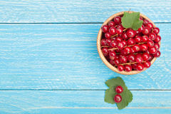 Red currant berries in a wooden bowl with leaf on the blue wooden background with copy space for your text. Top view Stock Images