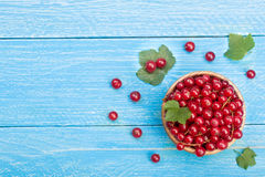 Red currant berries in a wooden bowl with leaf on the blue wooden background with copy space for your text. Top view Royalty Free Stock Images