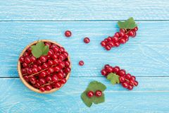 Red currant berries in a wooden bowl with leaf on the blue wooden background. Top view Royalty Free Stock Photos