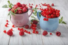 Red currant and raspberries. Red currant in a blue mug next to the raspberries in the pink mug Royalty Free Stock Images