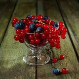 Red currant and blueberries. Berries in a glass vase on an old wooden table Royalty Free Stock Photo