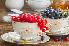 Red currant and blueberry in cups. On wooden table Royalty Free Stock Images