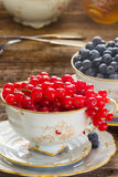 Red currant and blueberry in cups. On wooden table Royalty Free Stock Photo