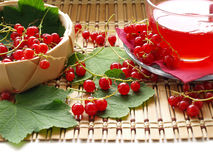 Red currant. Busket with red currant and cup on wooden dask Royalty Free Stock Images
