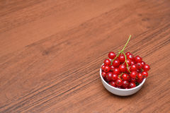 Red currant and cherry in the white plate on a wooden table Royalty Free Stock Photos