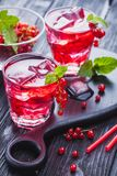 Red currant cocktail with ice and fresh mint on a black wooden table Stock Photos