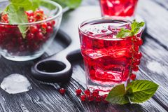 Red currant cocktail with ice and fresh mint on a black wooden table Royalty Free Stock Images