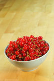 Red currant fruits in a bowl. On a wooden table Royalty Free Stock Photography