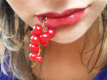 Red currant in lips Stock Photography