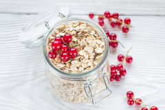 Red currant and oat flake in mason jar. Mason jar of oat flake, berries  on white wooden  background - health and diet concept (with easy removable sample text Stock Images