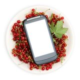 Red currant in plate and smartphone with a white screen mock up isolated on white background top view, copy space. Technology Inte Royalty Free Stock Photo