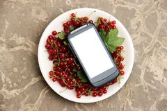 Red currant in plate and smartphone with white screen mock up on stone countertop, top view, copy space. Technology Internet in ag. Riculture. Applications for Royalty Free Stock Photography