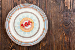 Red currant on a plate. On wooden background royalty free stock photography