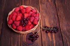 Red currant and raspberry in a basket on a wooden background. Close-up Stock Images