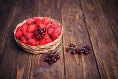 Red currant and raspberry in a basket on a wooden background. Close-up Stock Image