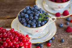 Red currant, raspberry and blueberry in cups. Blueberry and fresh berries in cups on wooden bckground Stock Photography