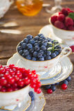 Red currant, raspberry and blueberry in cups. Blueberry and fresh berries in cups on wooden table Royalty Free Stock Photography